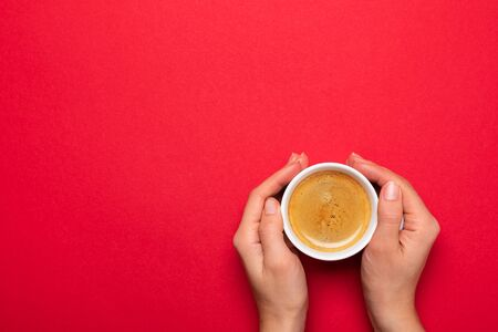 Female hand holding a white cup with black coffee on a red background. Banque d'images - 137371320