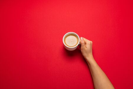 Female hand holding a white cup with black coffee on a red background. Banque d'images