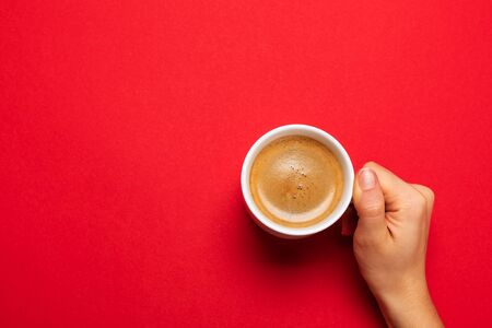 Female hand holding a white cup with black coffee on a red background. Zdjęcie Seryjne