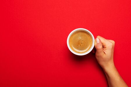 Female hand holding a white cup with black coffee on a red background. Banque d'images - 137371360