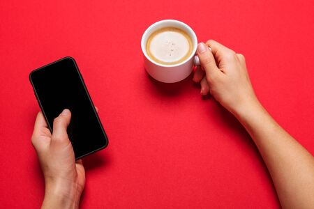 A Cup of coffee and a modern smartphone. black screen. red background. Banque d'images - 137371294
