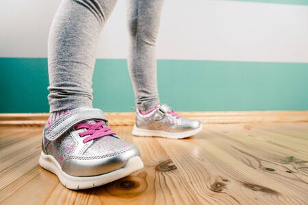 child in sneakers on wooden background Banque d'images