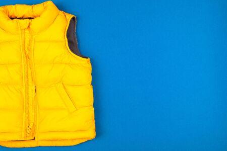 Yellow kids jacket isolated on blue background