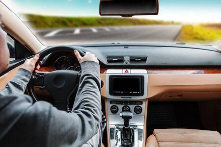 The man driving the modern car