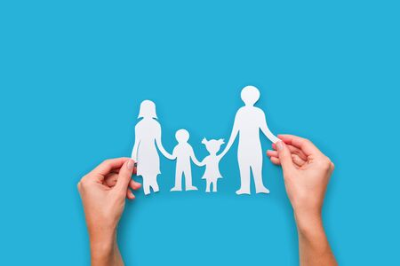 Paper family in hand isolated on blue background Stock Photo - 137371273