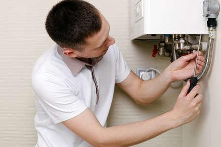 a man repairing a boiler in a medical mask 免版税图像