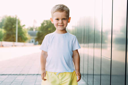 little boy in white t-shirt. space for your logo or design. Mockup for print 免版税图像