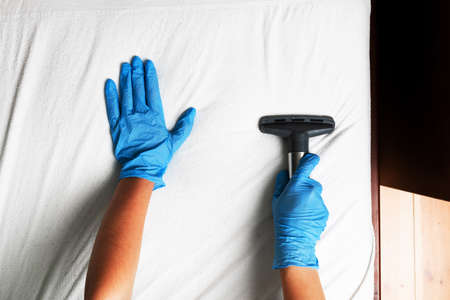 Janitor cleaning mattress with professional equipment in bedroom, closeup 免版税图像