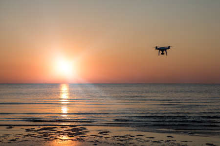 flying drone on a background of sea sunset
