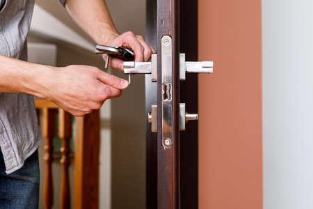 a man repairing a doorknob
