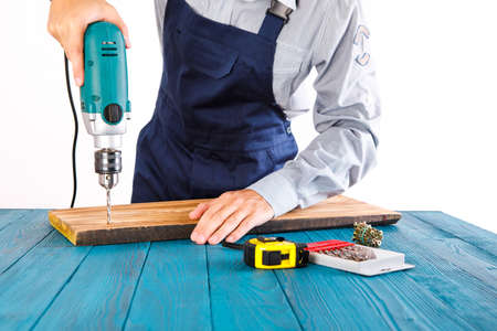 Handyman in blue uniform works with electricity automatic screwdriver. House renovation conception.