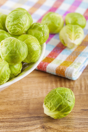 overhead shot: Overhead shot of brussels sprouts in a ceramic bowl and on a wooden table with a cloth rag.