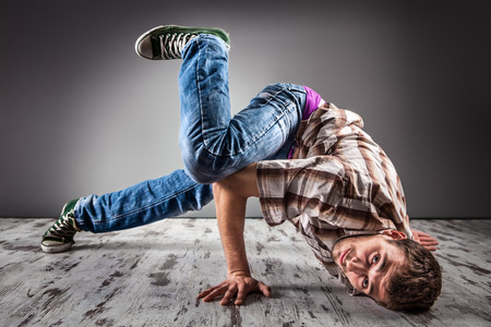 aerobica: Young caucasian man performing break dance over a gray background