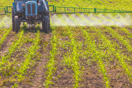 A tractor field sprayer spreading herbicide onto field photo