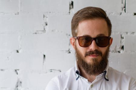 estilo urbano: Hombre joven con la barba y el bigote en gafas de sol delante de la pared de ladrillo blanco Foto de archivo