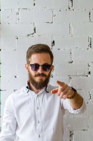 men standing: Young man with beard and mustache in sunglasses in front of white brick wall