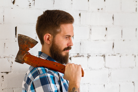 strong men: Young bearded lumberjack in blue shirt with red axe Stock Photo