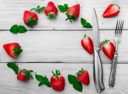 stell: Strawberry, stainless stell knife and fork , leaf of mint slice of strawberry.White wooden background.Free space in the middle.Round composition