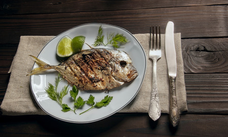 dill and parsley: Grilled fish (Vomer) lime ,dill,parsley on the white plate with knife and fork.top view