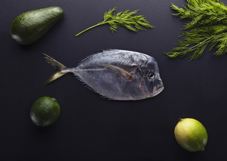 natue: Fresh fish (Vomer or Selene setapinnis ) dill, lime and lemon on the dark stone background.Flat lay. Top view.