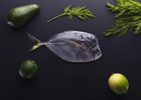 Verse vis (Vomer of Selene setapinnis) dille, limoen en citroen op de donkere steenachtergrond. Bovenaanzicht.