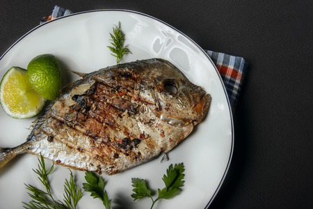 dill and parsley: Grilled fish (Vomer) lime ,dill,parsley on the white plate.closeup