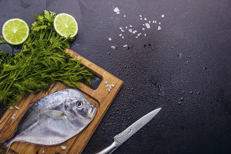 natue: Fresh fish (Vomer or Selene setapinnis ) lay on the wooden desk ,dill,parsley, knife, lime scattered sea salt. dark stone background.Flat lay. Top view.Drop water Stock Photo