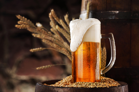 Mug of light beer pills with foam on a wooden barrel against stone wall. 免版税图像