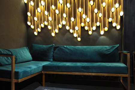Modern lounge bar interior.Dark tone.Dark cyan sofa .Golden laterns in form of tubes. 免版税图像