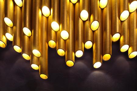 Golden tube lamp. texture. closeupCreative modern lamp 免版税图像