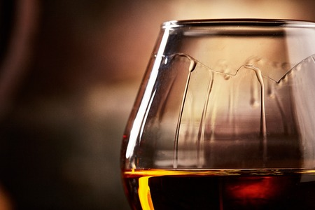glass with cognac closeup.taste of cognac.Macro shot of cognac closeup