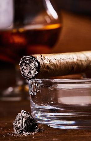 close view on smoking cuban cigar with ash
