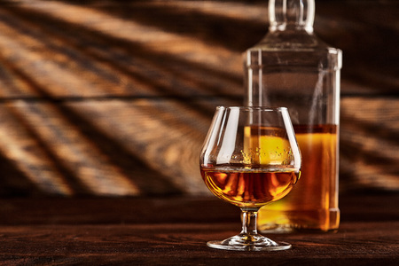 Glass and bottle of Cognac on wodden table.Wooden background 免版税图像