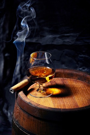 Cognac and Cigar on old oak barrel.Blue stone background