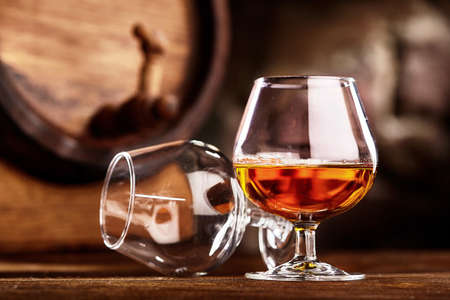 Two glass of Cognac and old oak barrel defocussed 免版税图像