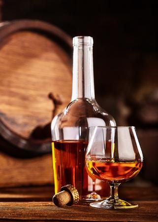 Glass and bottle of Cognac on wodden table old oak barrel defocussed
