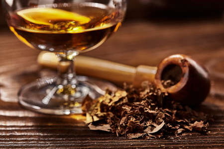 tobacco and drefocused glass of cognac and pipe on wooden table