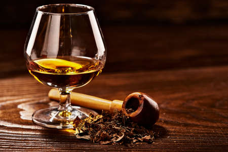 Glass of cognac and pipe with tobacco on wooden table