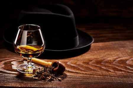 Glass of cognac and pipe with tobacco with black hat defocused on second background on wooden table 免版税图像