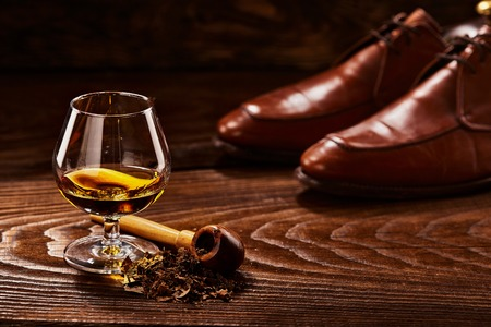Glass of cognac and pipe with tobacco with glance shoes defocused on second background on wooden table