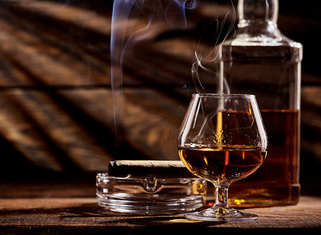 Glass of cognac or brandy with smoking cigar on wooden table