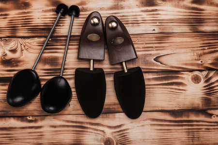 Two pairs of shoetree on the vintage background fired wood.