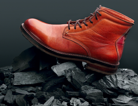 Stylish advertising of brown leather boots polish.Waxing boots.On charcoal