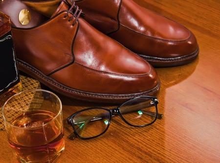 Eyeglassesand Glass of whiskey,waxing derby shoes shine.Luxury.