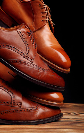 Four toes one on one of brown shoes brogues and derby on the wooden table.Shoes shine concept of luxury shoes 免版税图像