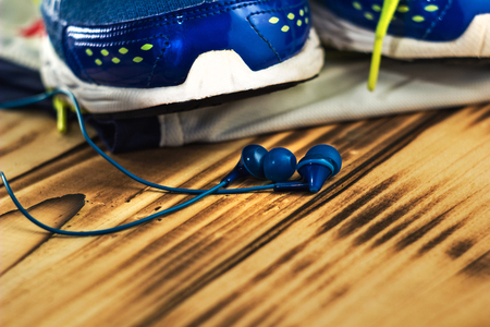 sneakers and earphones on the old wooden textures. 免版税图像