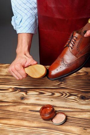 Shoes master (man) polishing leather shoes with brush