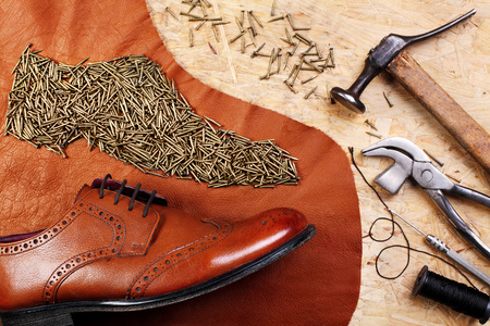 Leather brogues shoes on pieces of leather and nails ordered in form of a shoe on table of shoemaker with cobbler tools.Creative image