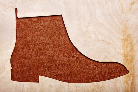 Silhoutte of leather chelsea boots in the center.Top view.Wooden background.Concet shoes shop Stock Photo
