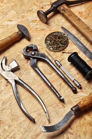 Set of cobbler vintage tools on the wooden background. Top view